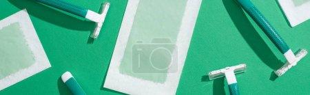 Photo pour Vue de dessus des rasoirs jetables verts et des rayures de cire d'épilation sur fond vert, prise de vue panoramique - image libre de droit