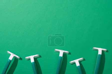 top view of green disposable razors on green background