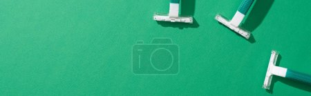Photo for Top view of green disposable razors on green background, panoramic shot - Royalty Free Image