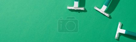 top view of green disposable razors on green background, panoramic shot