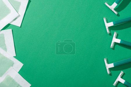 Foto de Vista superior de maquinillas de afeitar desechables verdes y rayas de cera depilación sobre fondo verde con espacio de copia - Imagen libre de derechos