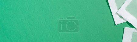 Foto de Vista superior de las rayas de cera de depilación sobre fondo verde con espacio de copia, disparo panorámico. - Imagen libre de derechos