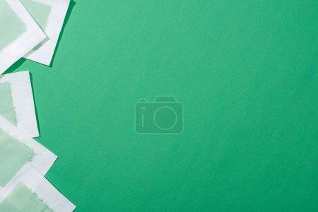 Foto de Vista superior de rayas de cera de depilación verde en fondo verde con espacio de copia. - Imagen libre de derechos