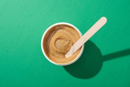 Photo pour Vue du dessus de la cire d'épilation en tasse avec bâton sur fond vert - image libre de droit