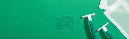 """Photo pour Vue du haut des rasoirs jetables verts et des bandes de cire d """"épilation sur fond vert avec espace de reproduction, photo panoramique - image libre de droit"""