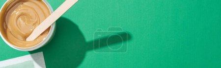 Photo pour Vue de dessus de cire verte et bande d'épilation sur fond vert, vue panoramique - image libre de droit