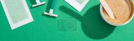 Photo pour Vue de dessus des rasoirs jetables verts, de la cire et des rayures d'épilation sur fond vert - image libre de droit