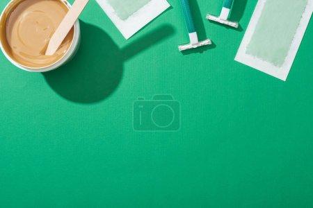Photo pour Vue du haut des rasoirs, de la cire et des bandes de dépilation jetables verts sur fond vert - image libre de droit