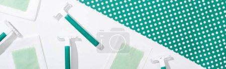 Photo pour Vue de dessus des rasoirs jetables verts et des rayures de cire d'épilation sur fond vert et blanc pointillé, prise de vue panoramique - image libre de droit