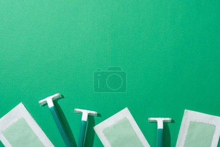 """Photo pour Vue du haut des rasoirs jetables verts et des bandes de cire d """"épilation sur fond vert avec espace de reproduction - image libre de droit"""
