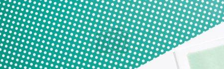 Photo pour Vue de dessus de la bande de cire d'épilation sur fond vert et blanc pointillé, prise de vue panoramique - image libre de droit