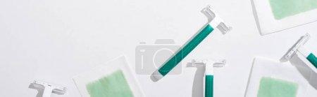 Photo pour Vue de dessus des rasoirs verts et des rayures de cire d'épilation sur fond blanc, vue panoramique - image libre de droit