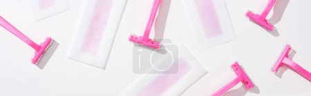 Photo pour Vue de dessus des rasoirs roses et des rayures de cire d'épilation sur fond blanc, vue panoramique - image libre de droit