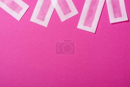 Photo pour Vue de dessus des bandes d'épilation de cire sur fond rose - image libre de droit