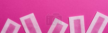 Photo for Top view of wax depilation stripes on pink background, panoramic shot - Royalty Free Image