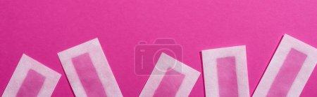 Photo pour Vue de dessus des bandes d'épilation de cire sur fond rose, prise de vue panoramique - image libre de droit