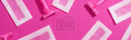 Foto de Vista superior de las rasquetas desechables y las rayas de depilación de cera sobre fondo rosado, disparo panorámico. - Imagen libre de derechos