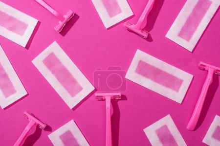 Foto de Vista superior de las rasquetas desechables y las rayas de depilación de cera sobre fondo rosado. - Imagen libre de derechos