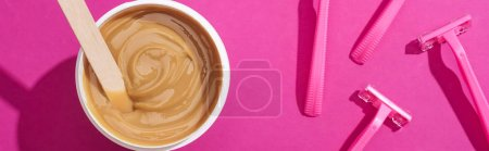 Photo pour Top view of disposable razors and depilation wax in cup with stick on pink background, panoramic shot - image libre de droit