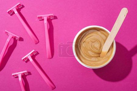 Photo pour Vue du dessus des rasoirs jetables et de la cire d'épilation dans une tasse avec bâton sur fond rose - image libre de droit