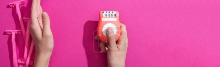 Photo for Cropped view of woman moving away disposable razors and taking epilator on pink background, panoramic shot - Royalty Free Image