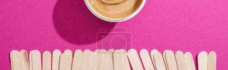 """Photo pour Vue du dessus de la cire d """"épilation dans un contenant avec bâtonnets sur fond rose, plan panoramique - image libre de droit"""