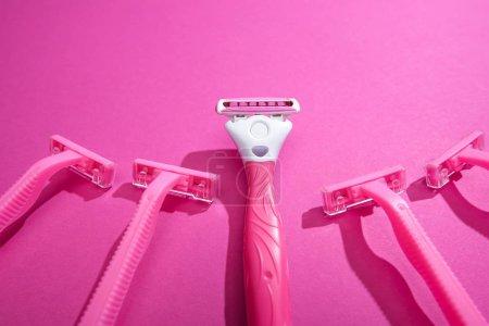 rasoirs féminins sur fond rose avec espace de copie