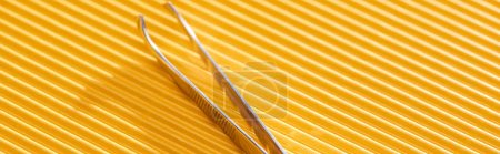 Photo for Stainless steel tweezers on yellow textured background, panoramic shot - Royalty Free Image
