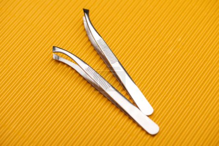 Photo for Stainless steel tweezers on yellow textured background - Royalty Free Image