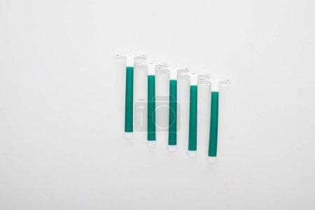 Photo pour Couché plat avec des rasoirs jetables verts sur fond blanc - image libre de droit