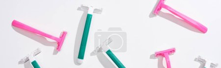 Photo for Top view of female pink and green disposable razors on white background, panoramic shot - Royalty Free Image