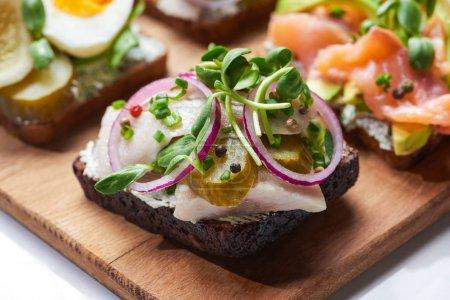 selective focus of of herring fish fillet on tasty danish smorrebrod on white
