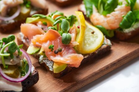 Photo for Selective focus of salmon fillet near sliced lemon on tasty smorrebrod sandwich - Royalty Free Image