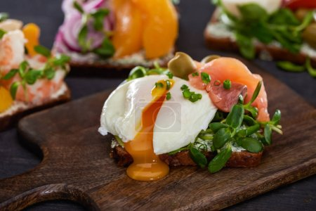 Photo for Close up of danish smorrebrod sandwich with poached egg near fresh salmon on wooden cutting board - Royalty Free Image