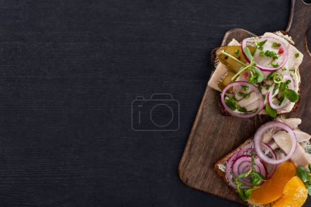 Photo for Top view of tasty smorrebrod sandwiches on rye bread on grey surface - Royalty Free Image