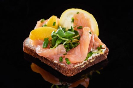 Photo for Close up of salmon on delicious smorrebrod sandwich on black - Royalty Free Image