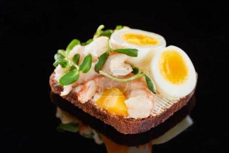 Photo pour Gros plan de pain de seigle avec crevettes sur sandwich smorrebrod sur noir - image libre de droit