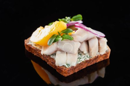 Photo for Close up of herring fish and canned peaches on prepared danish smorrebrod sandwich on black - Royalty Free Image