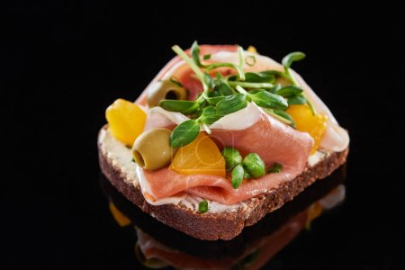 Photo for Selective focus of ham and olives on cooked danish smorrebrod sandwich on black - Royalty Free Image