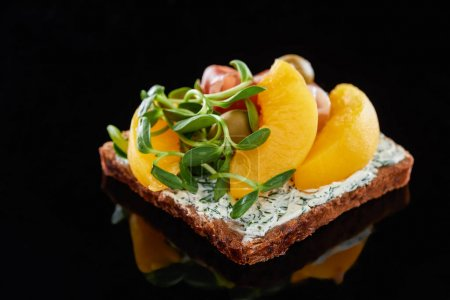 Photo for Selective focus of canned peaches on danish smorrebrod sandwich on black - Royalty Free Image