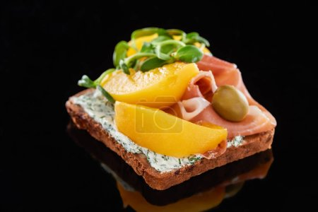 Photo for Selective focus of ham and canned peaches on danish smorrebrod sandwich on black - Royalty Free Image