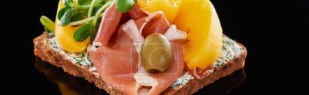 Photo pour Plan panoramique de jambon et pêches en conserve sur sandwich danois smorrebrod sur noir - image libre de droit