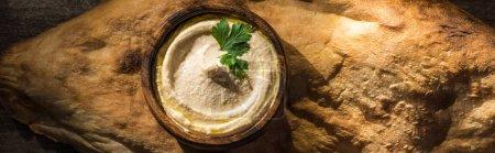 Photo pour Vue de dessus de délicieux houmous dans un bol sur pita fraîche cuite au four, panoramique - image libre de droit