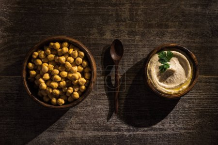 top view of delicious hummus and chickpeas in bowls near spoon on wooden rustic table