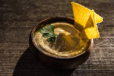 delicious hummus in bowl with nachos on wooden rustic table