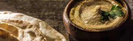 köstlicher Hummus in Schüssel neben frisch gebackener Flaka auf rustikalem Holztisch, Panoramaaufnahme