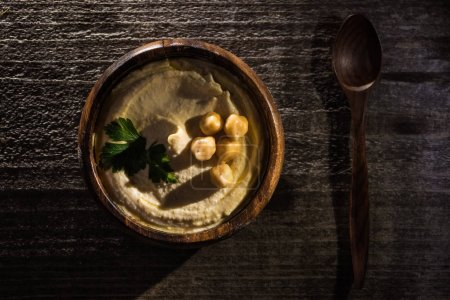 top view of delicious hummus with chickpeas in bowl on wooden rustic table