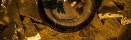 Photo pour Vue du dessus de délicieux houmous aux pois chiches dans un bol près des nachos, panoramique - image libre de droit