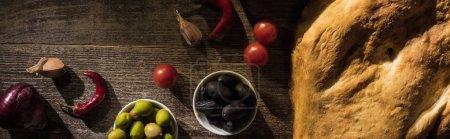 Draufsicht auf köstliche Flava, Gewürze und Oliven auf rustikalem Holztisch, Panoramaaufnahme