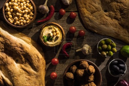 Photo for Top view of delicious falafel, hummus, chickpeas, pita, vegetables and olives on wooden rustic table - Royalty Free Image